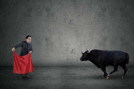 toro: El hombre de negocios de pie delante de toro furioso, mientras sostiene una tela roja