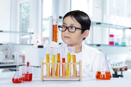 experimento: Pequeño colegial en la lección de química, haciendo experimento químico en el tubo de ensayo, un tiro en el laboratorio