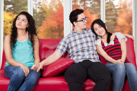 couple on couch: Caucasian man sitting on the sofa with his girlfriend while holding hands with his affair Stock Photo