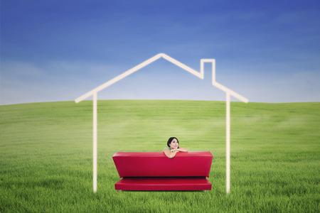 soñando: Hembra asiática soñando con una casa en el sofá rojo en el campo verde