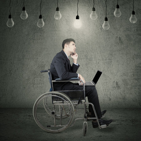 success man: Portrait of young disabled businessman sitting on wheelchair under lamps while holding laptop and thinking idea