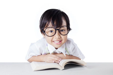 asia children: Portrait of little schoolgirl wearing glasses and smiling on the camera while reading a book on desk, isolated on white