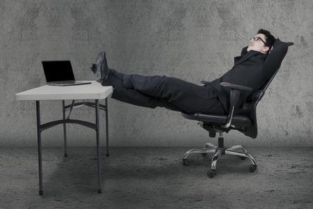 soñando: trabajador caucásico joven que se relaja en el sillón con los pies sobre el escritorio y soñando despierto Foto de archivo