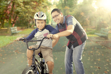 Portrait of young father teaching his son to learn how to ride a bicycle on the road at the park Stock Photo
