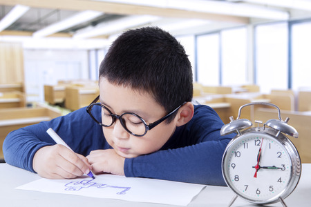asian boy: Cute little student drawing on the paper while wearing a glasses in class with a clock on desk