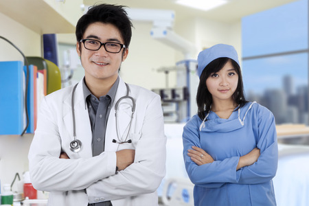 doctors smiling: Confident asian doctors folded arms and smiling at camera in hospital