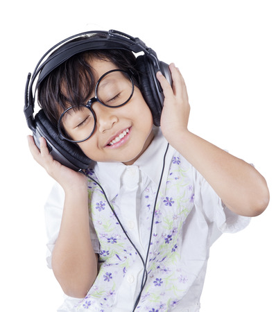 listening: Cute small girl wearing glasses and enjoy music by using headphones, isolated on white background