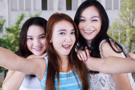 three girls: Gorgeous female students taking self picture together at school yard