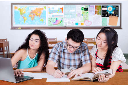 high: Portrait of three multi ethnic students studying together in the classroom