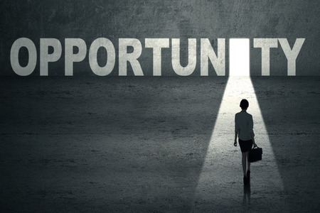 Businesswoman walks toward an opportunity door