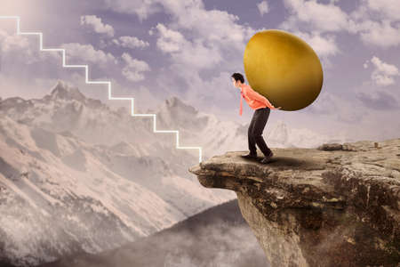 golden egg: Businessman is carrying big golden egg to the top via virtual stairs