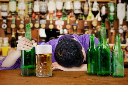 borracho: Hombre de negocios borracho e inconsciente tirado en un contador en un bar Foto de archivo