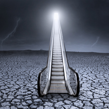 light at the end of the tunnel: Escalator on a cracked ground in a stormy day symbolizing way to escape from an economic crisis Stock Photo