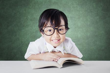 colegiala: Colegiala adorable que lleva gafas y sonriente en la c�mara, mientras que la lectura de una literatura en el aula