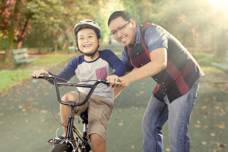 riding helmet: Cute little boy try to ride a bike with his father on the road at the park, shot outdoors