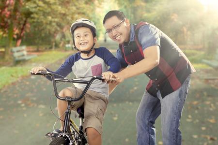Mignon petit garçon essayer de faire du vélo avec son père sur la route dans le parc, filmé en extérieur