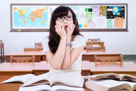 asustado: Retrato de estudiante de secundaria femenina sentada y el estudio en el aula con expresión de miedo