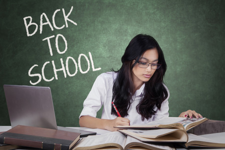 girl studying: Beautiful female student with long hair, back to school and studying in the class with laptop and books
