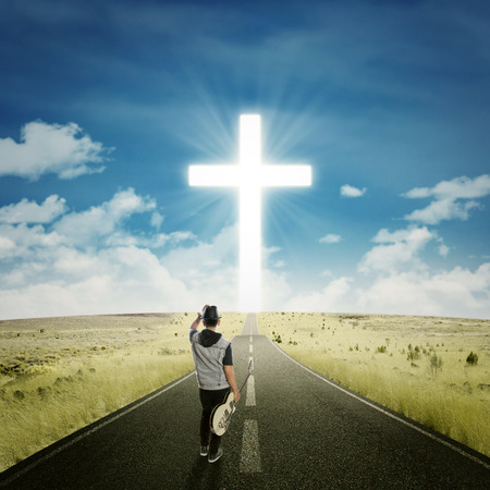 christian: Rear view of young singer holding a guitar while walking on the highway to the cross Stock Photo
