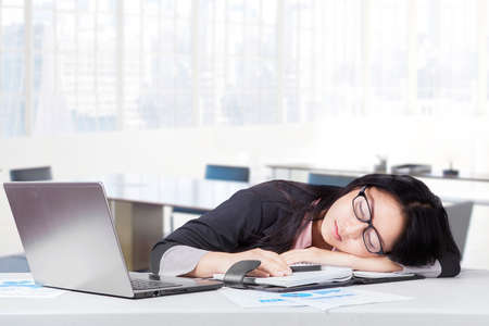 exhausted: Portrait of female worker wearing formal suit relaxing and sleeping in office with laptop in office