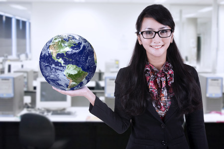 environmental suit: Businesswoman is holding world globe at office Stock Photo