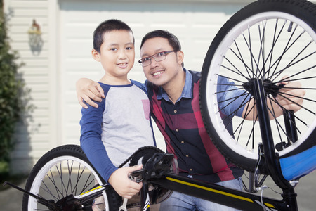 garage on house: Portrait of little boy and his dad, smiling at the camera after repairing a bicycle at the garage