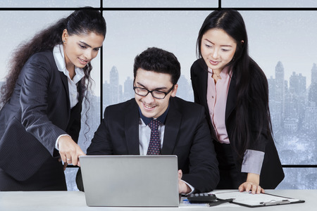 team working: Portrait of young businesswoman showing document on laptop to her partners in the office Stock Photo
