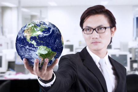 asian businessman: Asian businessman looking smart with glasses holding a globe at office
