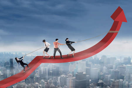 financial team: Four workers work together to pull and climb a business graph upward Stock Photo