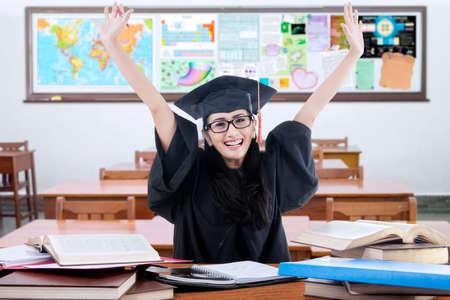 graduado: Estudiante graduada femenina que lleva vestido de graduación feliz en el aula y elevar las manos