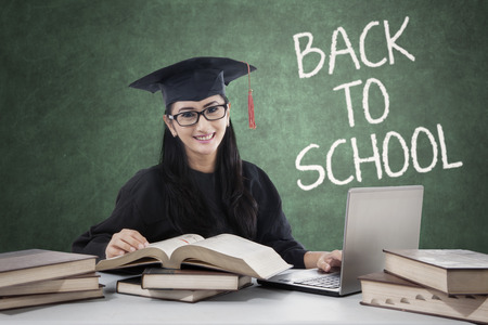 mortarboard: Female high school student with mortarboard back to school and studying in the class with laptop and books
