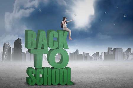 mochila escolar: Estudiante femenino que se sienta en un texto de nuevo a la escuela y la liberación de palomas