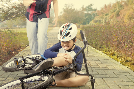 Petit garçon pleurer sur la route tout en tenant son genou après une chute de la bicyclette avec son père à l'arrière