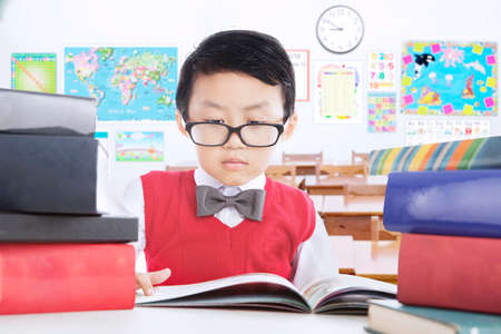 asia children: Cute little boy studying in the classroom and reading lesson books while wearing glasses, shot in the school