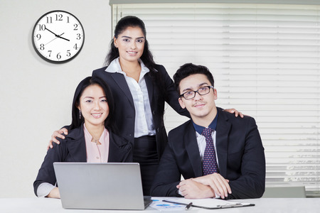 multi racial: Portrait of three multi racial corporate worker wearing formal suit and smiling on the camera in the office