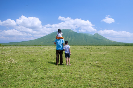 Father and children looking at mountain view, shot on springtime Stock Photo