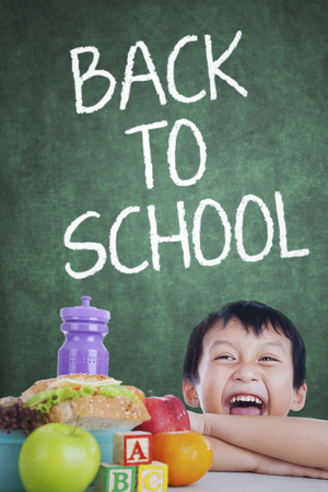 tupperware: Portrait of of cheerful little boy back to school with his lunch on the table