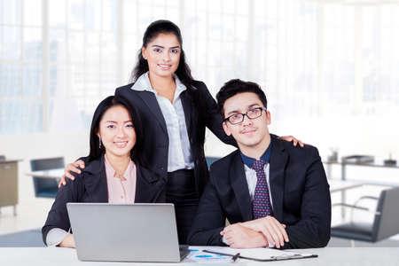 personas mirando: Grupo de empresarios multirracial con traje formal mirando y sonriendo a la c�mara en la oficina