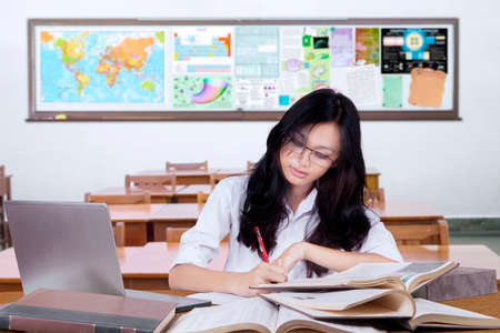 hispanic girl: Portrait of beautiful female learner with long hair doing her task on the table in the classroom Stock Photo