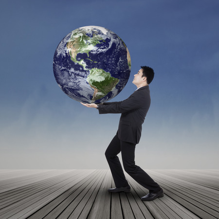businessman carrying a globe: Young asian businessman trying to save the world