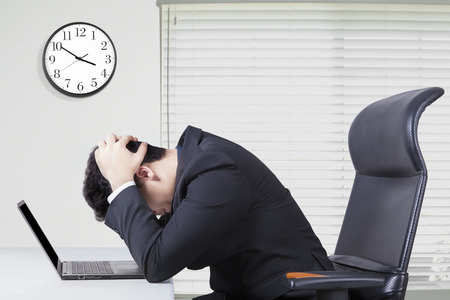confundido: Joven empresario sentado en la oficina y se ve confundida con un ordenador portátil en el escritorio y el reloj en la pared