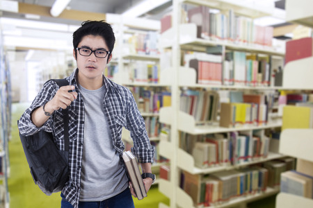arrogant teen: Male arrogant student pointing at camera in the library