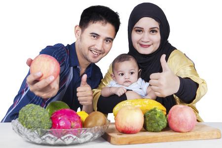 comida rica: Retrato de familia feliz con su bebé y las frutas frescas, mostrando el pulgar hacia arriba en la cámara, aislado en blanco Foto de archivo