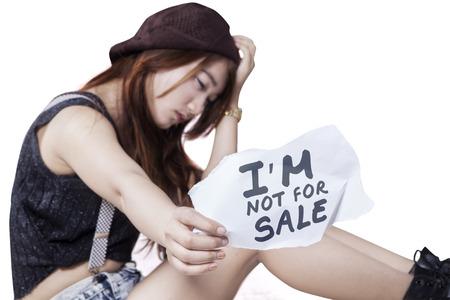 prostituta: Víctima Muchacha deprimida de la trata de personas, sentado solo en el estudio y que muestra un documento