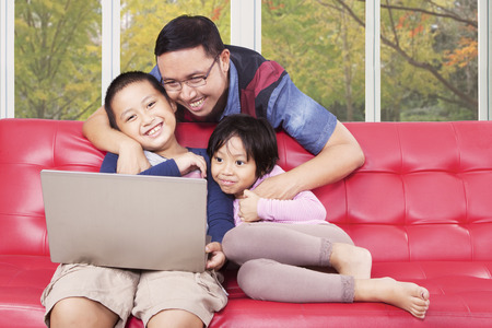 attractive couch: Two cheerful children using laptop computer for watching movie with their father at home