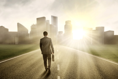 career: Young manager carrying a briefcase while walking on the road toward a city