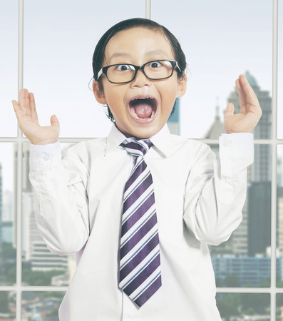 shocked: Attractive little boy wearing a tie in the office and looks shocked