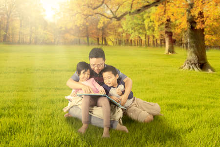 happy family nature: Two attractive children reading a story book with their dad while sitting at the autumn park Stock Photo