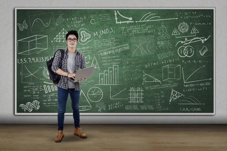 estudiantes: Apuesto estudiante de secundaria masculina de pie en clase mientras que la celebración de ordenador portátil Foto de archivo
