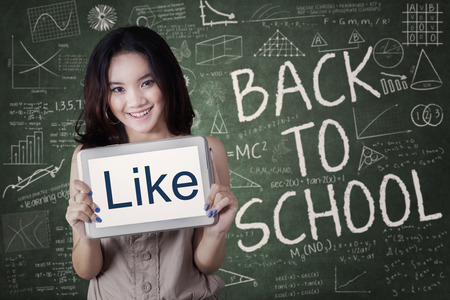ooking: Female student back to school and showing a LIKE icon with a tablet in the class